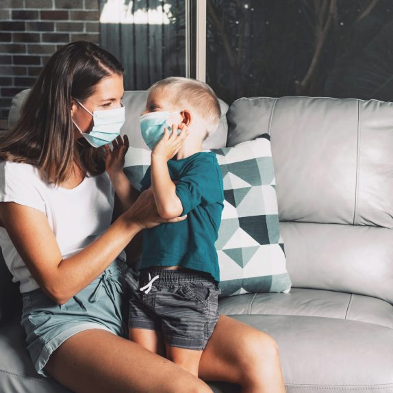 Mother and child wear facemask during coronavirus and flu outbreak staying at home. Virus protection. Mother and son trying to stop disease spread.
